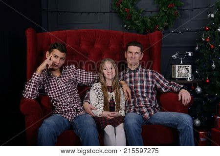 Happy father with teenage daughter and son are sitting in front of a Christmas tree in anticipation of Christmas.