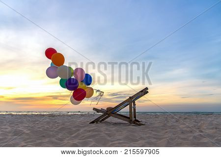 Multicoloured balloons with canvas bed for relax on sunset tropical beach sunny day. Summer Concept.