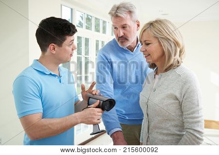 Security Consultant Demonstrating Alarm System To Mature Couple