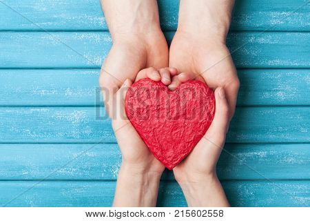 Woman and man hands holding red shape of heart. Saint valentine day background. Relationship family and donorship concept.