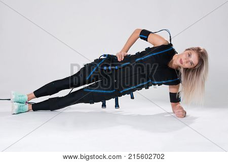 Beautiful Blonde In An Electric Muscular Suit For Stimulation Makes An Exercise On The Rug