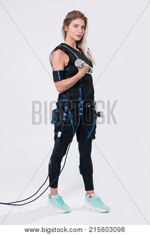 Beautiful Blonde In Electric Muscular Suit For Stimulation With Dumbbells