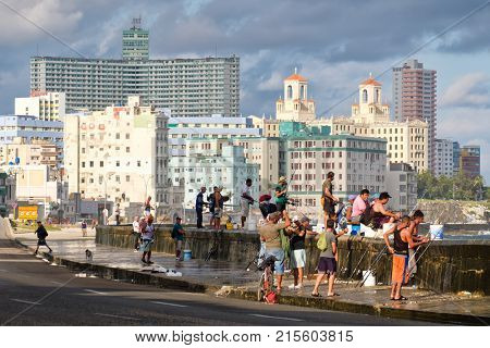 HAVANA,CUBA - NOVEMBER 25,2017 : Fishermen at the famous Malecon seawall in Havana with a view of the city skyline