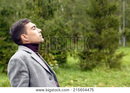 Portrait Of Young Attractive Man With A Grey Coat, Breathing In The Fresh Autumn Air In The Park, Sh