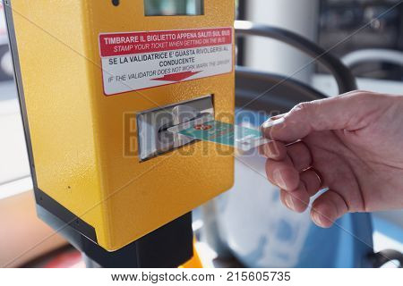 BERGAMO, ITALY - JUNE 11, 2017: Passenger stamping his ticket in the public bus operated by Azienda Transporti Bergamo. Founded in 1907, ATB operates in the area of Bergamo and 29 surrounding towns