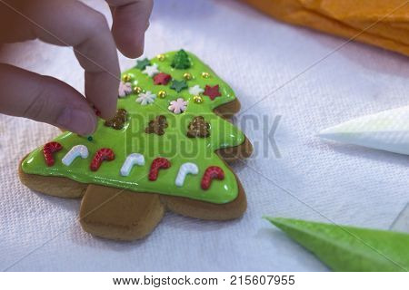 Child Hands Decorating Gingerbread With Icing Sugar Using A Pipping Bag. Christmas Treats. Handmade