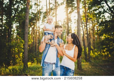 Stylish Young Family Of Mom, Dad And Daughter One Year Old Blonde Sitting Near Father On Shoulders,