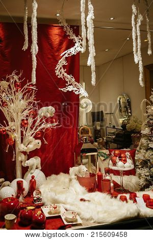 Christmas decorations in store window showcase of a floral show pin Strasbourg France with multiple colorful globes vases and toys