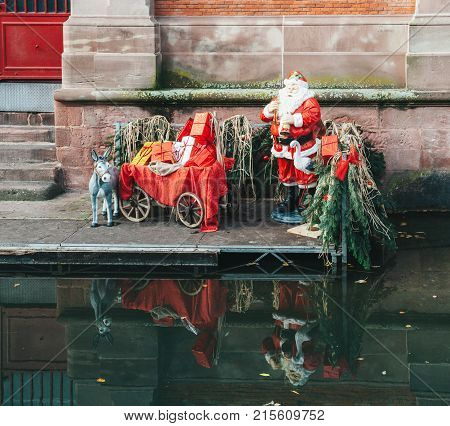 Statues of Santa Claus and his donkey with all the gifts near the Covered market of Colmar building with reflection in the Colmar Canal called Little Venice