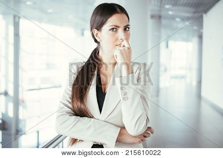 Closeup portrait of serious beautiful middle-aged business woman wearing jacket, touching chin, looking at camera and thinking in light office hall