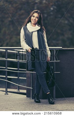 Happy young woman walking in city street. Stylish fashion model in long vest and white sweater outdoor