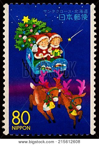 Moscow Russia - November 27 2017: A stamp printed in Japan shows children with christmas tree ride on reindeer sledge of Santa Claus circa 1999