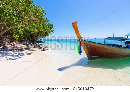 Traditional longtail boat moored at Aonang beach against clear blue sky