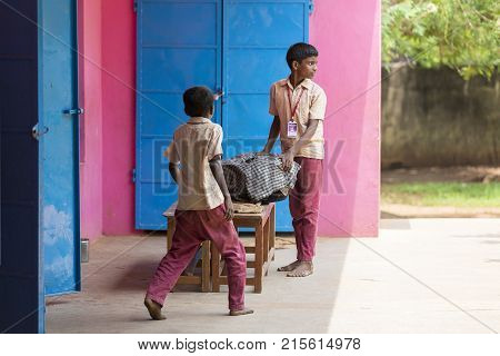 PONDICHERY PUDUCHERY INDIA - SEPTEMBER 04 2017. Unidentified boys children bring the plate to be served at the outdoor canteen.