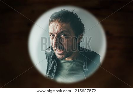 Angry man at the door viewed through spy hole debt collector or criminal knocking at the door