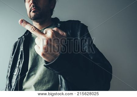 Angry male punk showing middle finger as form of aggressive impolite dissatisfaction gesturing. Retro toned selective focus.