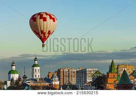 red and white balloon flies very low over the city, directly over the Christian Church in the clear cloudless sky on a windless day
