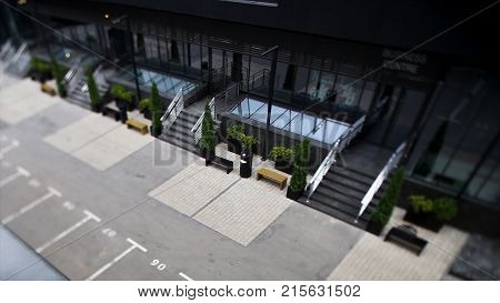 Parking entrance to office building with parking and benches. Facade of modern Business Center with glass doors. Large modern office building HD