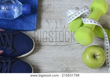 Fitness accessories. Sports dumbbells sneakers sports shoes and clothes. Women items for sports life. Measuring tape, centimeter. The concept of sport for weight loss.