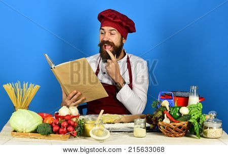 Man With Beard Holds Recipe Book Or Menu On Blue