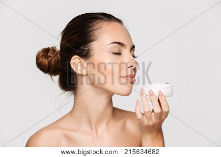 Beauty portrait of a pretty young half naked woman smelling container with a face creamisolated over white background