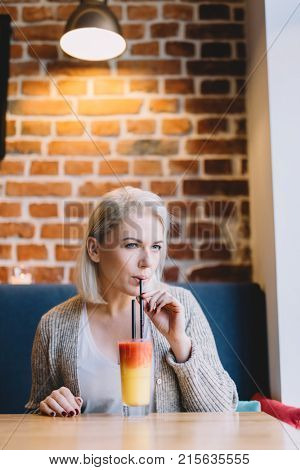 Young woman sipping a colorful drink with a straw in a cosy interior. Fit drink.