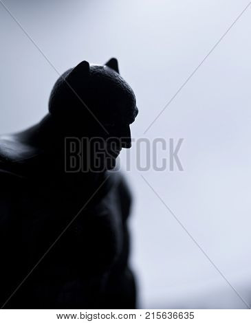 Studio image of Batman action figure silhouetted against backlit surface and dramatic lighting. Batman is a DC Comics character also known as the Dark Knight and Caped Crusader.