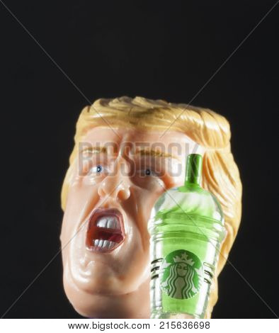 Studio image of an angry Donald Trump head and Starbucks Frappuccino. Trump often attacks Starbucks on Twitter over their Christmas coffee cup designs.