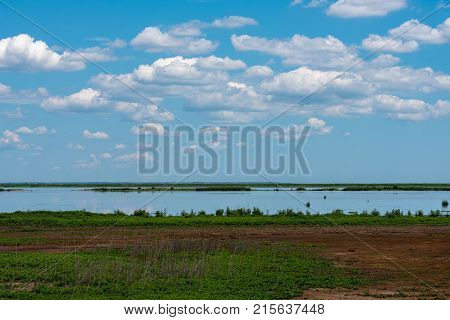 Puffy Wwite clouds in a blue sky hover over Marshlands with deep green grasses