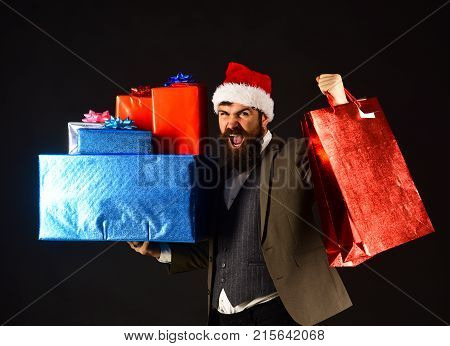 Manager with beard and pile of gifts. Man in smart suit and Santa hat on black background. Business and celebration concept. Businessman with excited face holds big present boxes and shopping bags