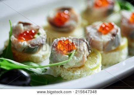 Cropped close up of canapes with fish and red caviar delicious fresh hunger appetite appetizers canape recipe traditional cusine restaurant cafe menu gourmet concept.