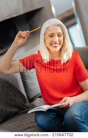 Sudden inspiration. Happy delighted positive woman holding her notebook and smiling while having a sudden inspiration