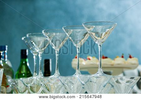 Close up shot of empty martini glasses on party table celebration festive gathering glassware dinnerware drinks champagne alcohol festife mood preparation serving.