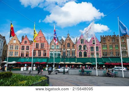 Bruges, Belgium - April 17, 2017: Tourists in north side of Grote Markt - Market Square of Bruges, Brugge, with enchanting street cafes, meeting place of the Brugelings and tourists.
