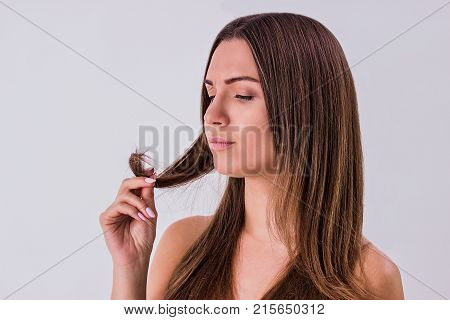 Some problems with her hair. Portrait of beautiful shirtless woman examining curl of hair in hand while standing against white background. Disappointed woman. Hair care and treatment concept