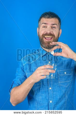 Man with beard hold water glass on blue background headache. painkiller drug and antidepressant. Treatment hypnotic tablet. Health and medicine flu and cold. happy hipster drink pill with water.