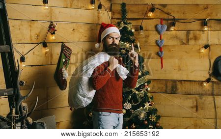 New year guy at Christmas tree with garland. Winter holiday and xmas. Santa claus man with gift pack. Boxing day and party celebration. Christmas man with beard on serious face at present sack.