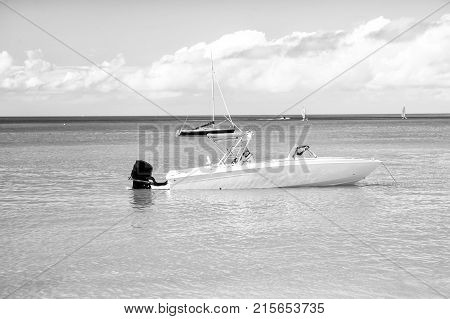 traveling and vacation sport and sailing man yachtsman on motorboat yacht on sea ocean water coast sunny summer outdoor on blue cloudy sky background in St. John Antigua