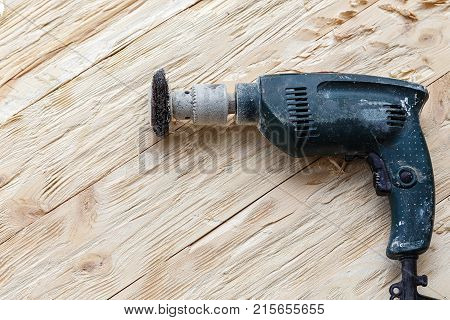 attachment on a drill scrape metal rotating brush. attachment is on a rough wooden surface