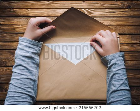A large brown envelope holds the child's hands. Envelope on a wooden background.