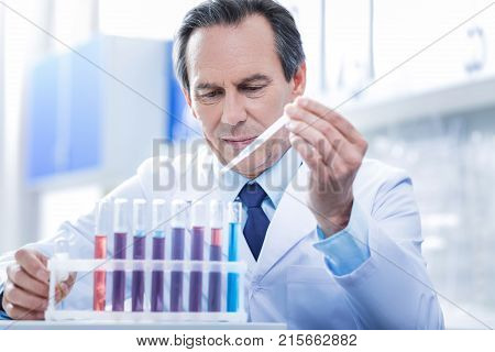Biological science. Serious nice professional biologist sitting at the table and looking at the test tubes while working with vaccine samples