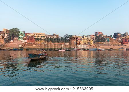 VARANASI INDIA - MARCH 15 2016: Horizontal picture from the boat of riverbank full of Ghats Temples and houses in Ganges River during sunrise in Varanasi India.