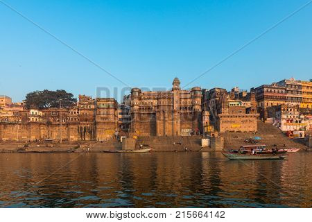 VARANASI INDIA - MARCH 15 2016: Front picture of amazing architecture of Munshi Ghat in Ganges River during sunrise in Varanasi India.