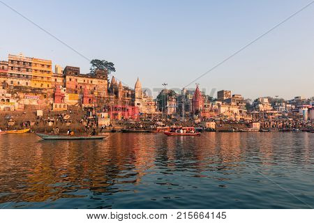 VARANASI INDIA - MARCH 15 2016: Wide angle picture of amazing architecture Dashashwamedh Ghat in Ganges River during sunrise in Varanasi India.