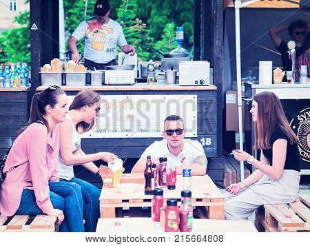 Vilnius Lithuania - June 9 2017: Young people eating fast food at Open Kitchen food festival in Vilnius Lithuania.