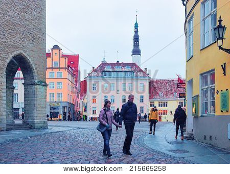 Tallinn Estonia - February 27 2017: Couple on Town Hall Square at the Old city of Tallinn Estonia in winter. Church of Holy Spirit on the background
