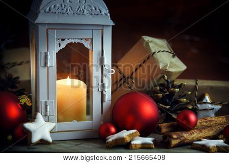 Christmas scene with lantern and a burning candle gifts in kraft paper red christmas ornaments pine cones and cinnamon star cookies on a rustic wooden background selected focus narrow depth of field