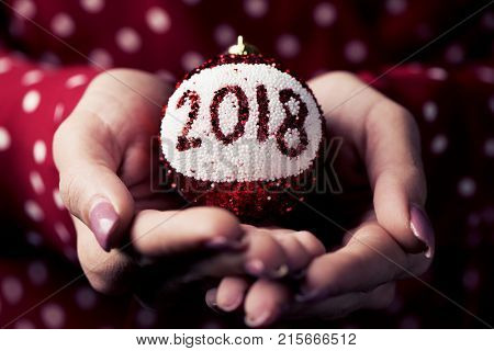 closeup a young caucasian woman wearing a red dress patterned with white dots holding a christmas ball in her hands with the number 2018, as the new year
