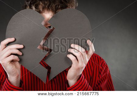 Love romance relationship heartbreak unhappy sadness shame concept. Man covering behind cutout. Young male hiding his face with parts of broken heart.