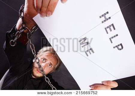 Stress depression assistance concept. Scared man with chained hands holding help me sign studio shot on dark grunge background